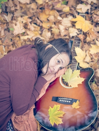 Beautiful girl resting on autumn leafs with guitar