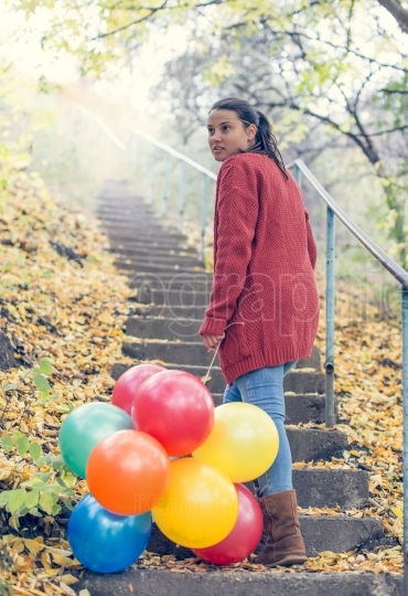 Beautiful girl with her balloons climbing stairs