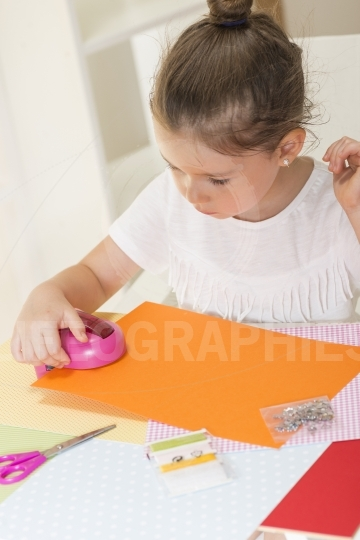 Beautiful little girl cutting paper using decorative drill press on the art lesson class
