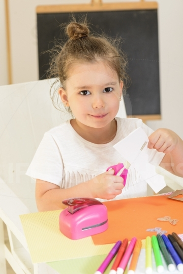 Beautiful little girl cutting paper with scissors on the art lesson class