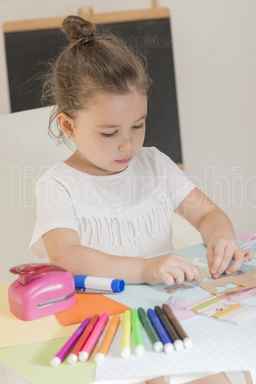 Beautiful little girl sticking pieces of paper on the art lesson class
