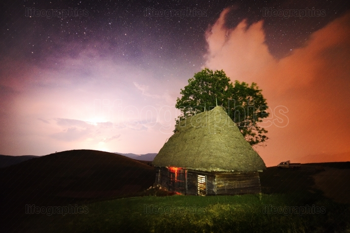 Beautiful night sky and silhouette of old rural house