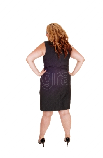 Beautiful plus sized woman standing in a black dress