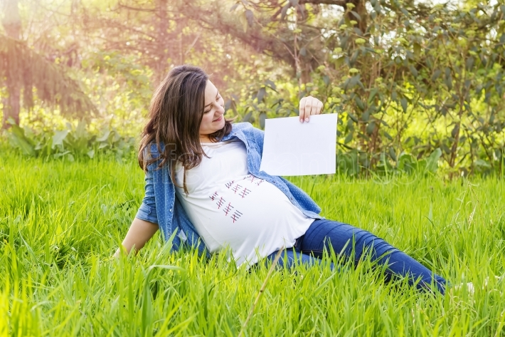 Beautiful pregnant woman outdoor with a paper in hand