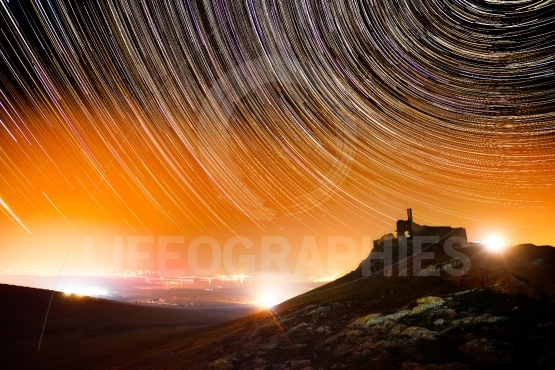 Beautiful sky at night with startrails and silhouette of old for