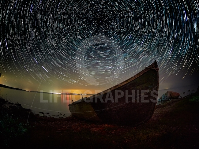 Beautiful sky at night with startrails over the lake and silhoue
