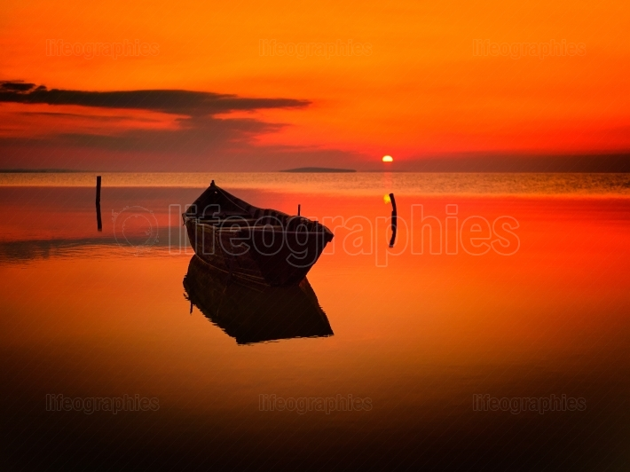 Beautiful sunset over water and silhouette fishing boat