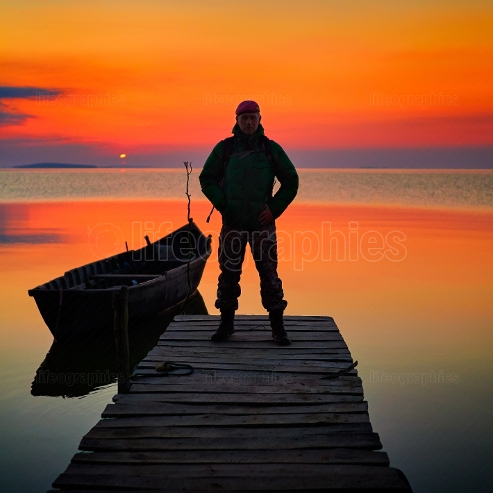Beautiful sunset over water and silhouette of man