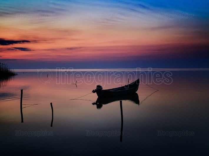 Beautiful sunset sunrise over water and silhouette fishing boat