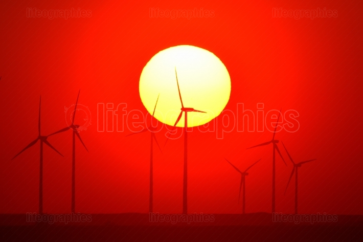 Beautiful sunset with wind turbines on the hill in summer, silho