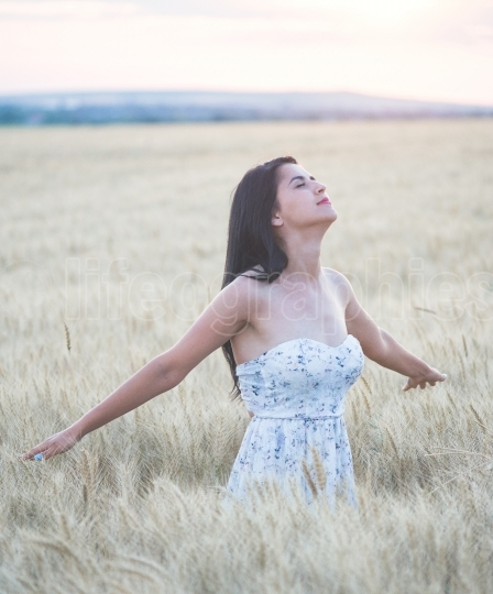 Beautiful woman in summer in wheat field at sunset