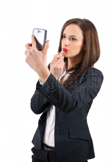 Beautiful woman making up using her phone like a mirror