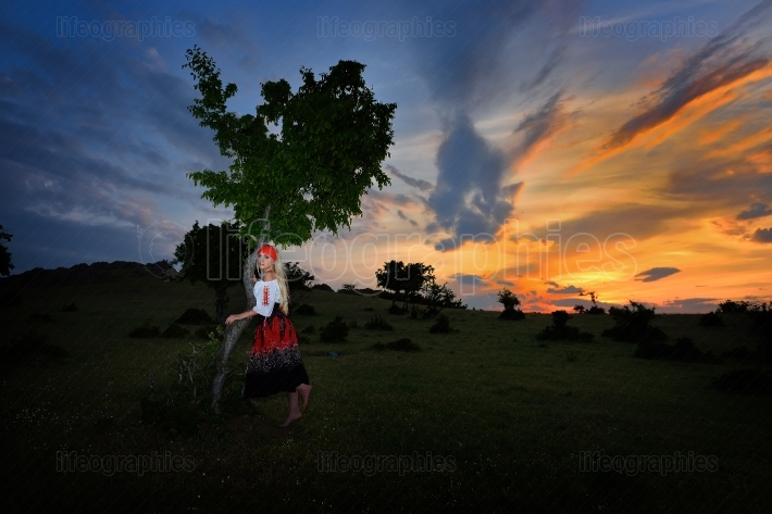 Beautiful woman on field at sunset