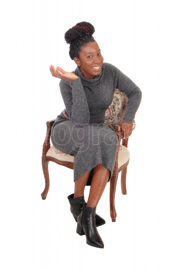 Beautiful woman sitting in a gray dress in an old chair