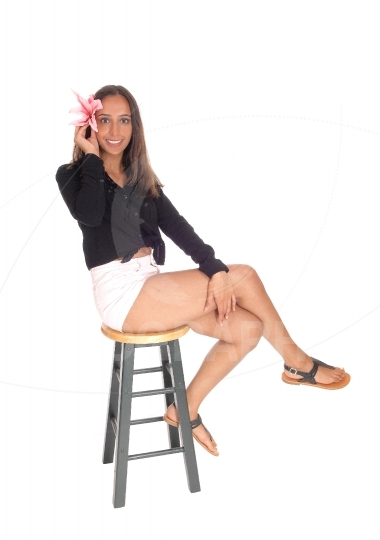 Beautiful woman sitting in shorts on chair