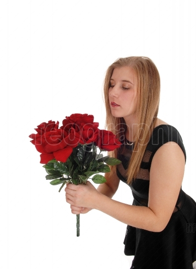 Beautiful woman with a big bunch red roses