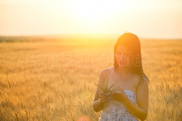 Beautiful woman with a wheat bouguet in wheat field at sunset
