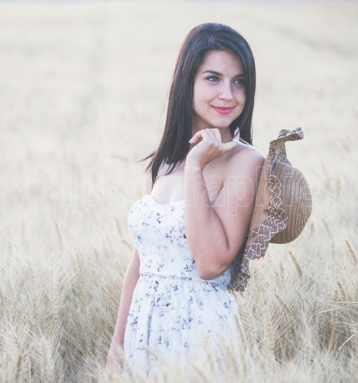 Beautiful woman with summer hat in wheat field at sunset