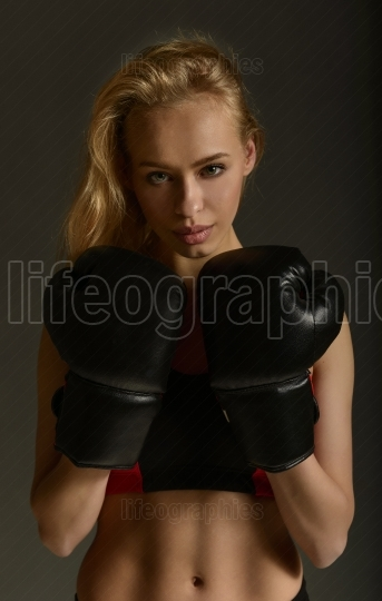 Beautiful young fit woman wearing black boxing gloves ready to exercise