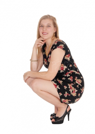 Beautiful young woman in a dress crouching