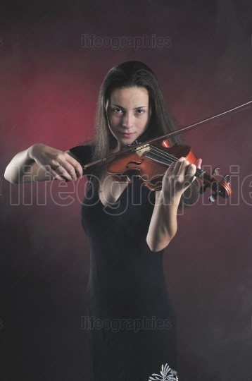 Beautiful young woman playing a violin over red foggy background.