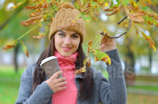 Beautiful young woman with beanie hat in park in autumn holding takeaway coffee cup, smiling.