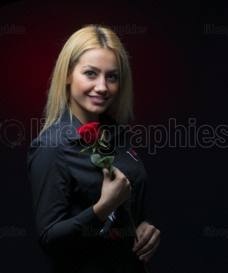 Beautiful young woman with red rose on dark background