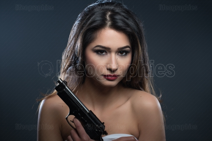 Beauty portrait of a woman with gun