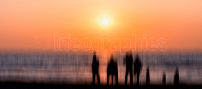 Big alien family silhouette meeting vivid orange sunset ocean ho