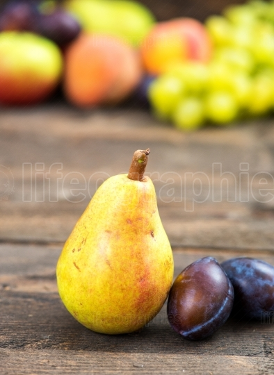 Bio pear and plums with other fruits in background
