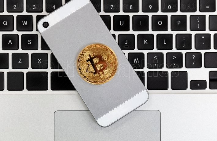 Bitcoin currency on smart phone with computer keyboard in backgr
