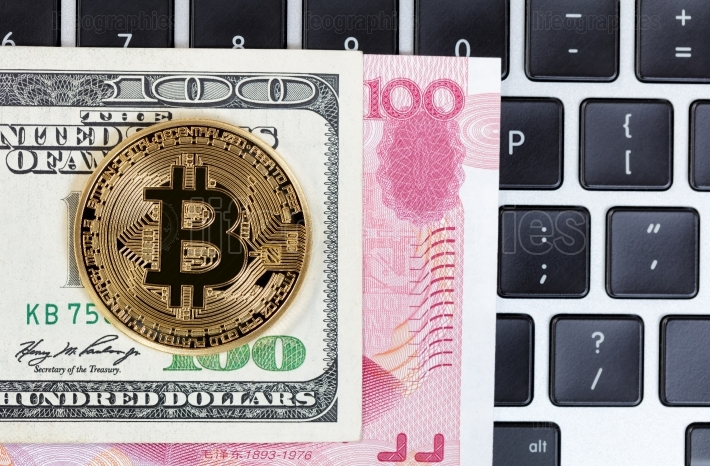 Bitcoin cyber single coin on keyboard with mixed paper currency