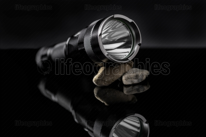Black flashlight on stones mirroring on black background
