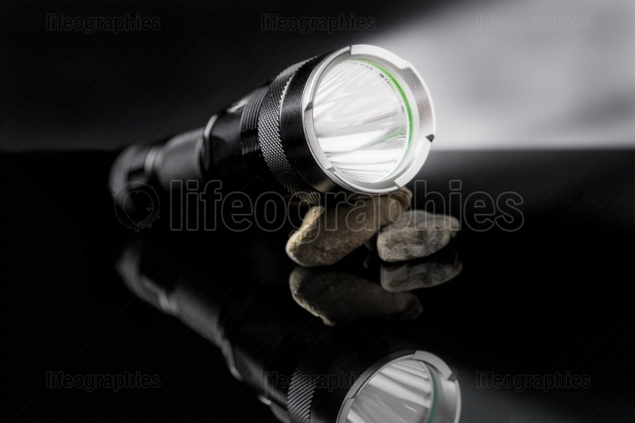 Black flashlight with lights open on stones mirroring on black b