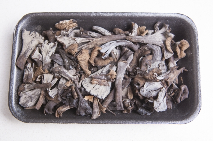 Black polythene tray full of Horn of Plenty mushrooms