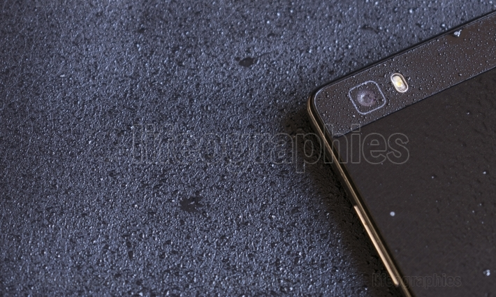 Black smart phone covered with water drops