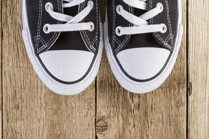Black sneakers on wood background