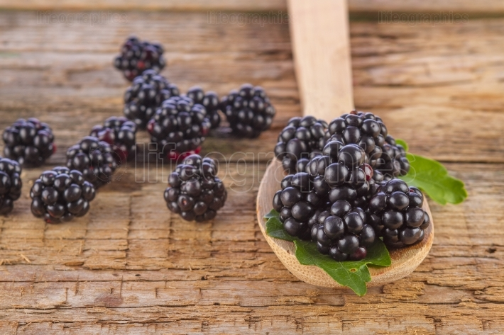 Blackberries in spoon on wooden background