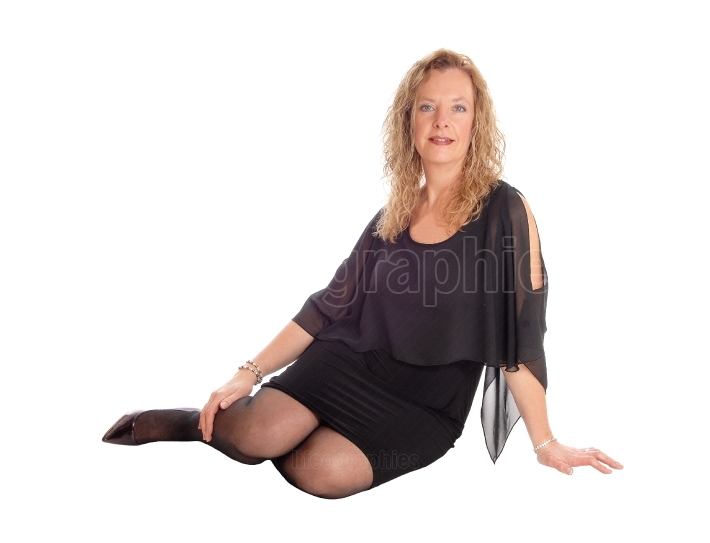 Blond woman in black dress sitting on floor.