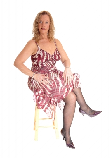 Blond woman sitting on chair.