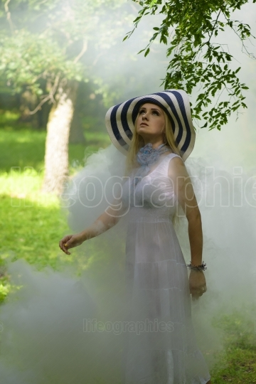 Blonde lady with big summer hat surounded by smoke