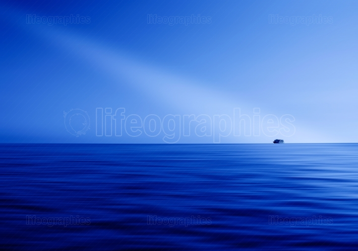 Blue ocean horizon ray of light abstraction with ship