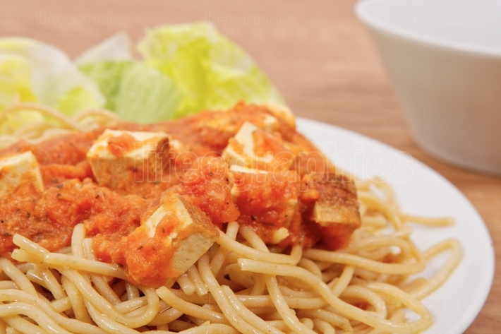 Bolognese spaghetti with tofu on a table