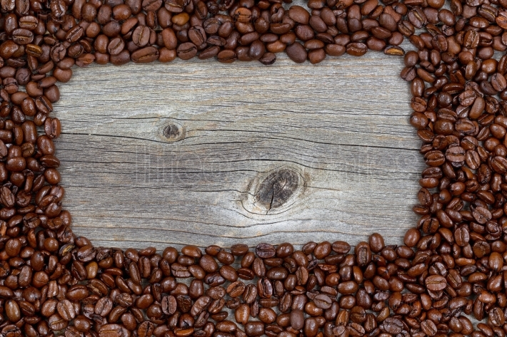Border of freshly roasted coffee beans on aged wood