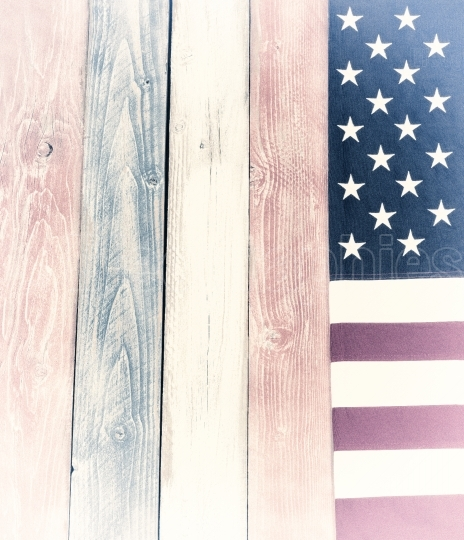Border of vintage USA flag on faded painted wooden boards in nat