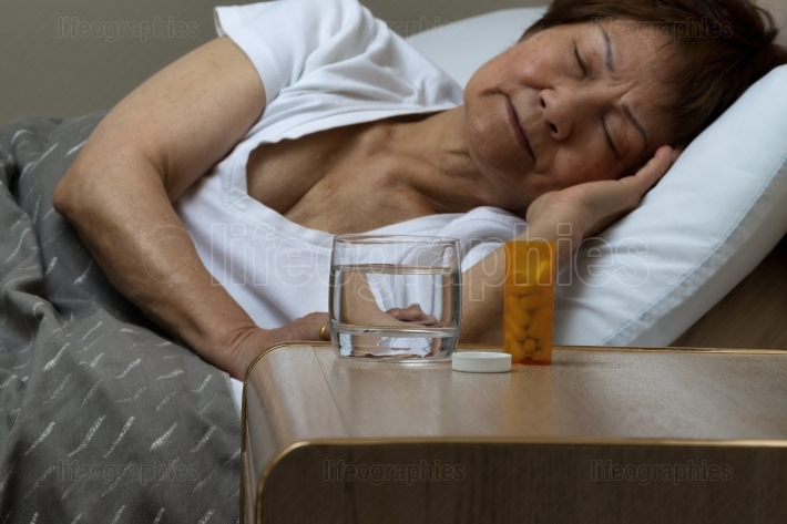 Bottle of medicine and water with senior woman sleeping in backg