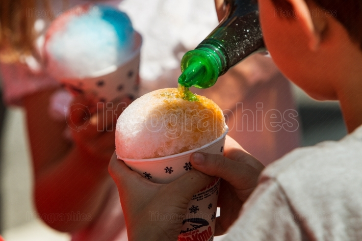 Bottle Pours Green Syrup Onto Snow Cone Held By Kid