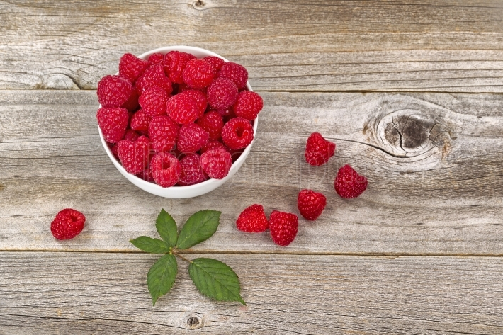 Bowl of Raspberries on aged wood