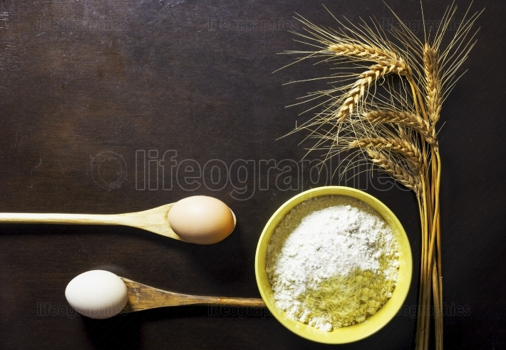 Bowl of wheat flour with wheat ears and eggs on wooden backgroun