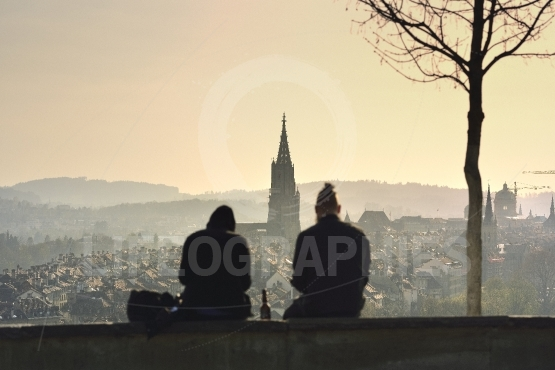 Boy and girl silhouette on sunset over old town of bern